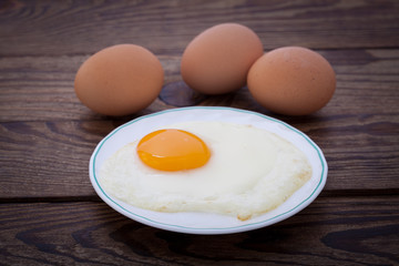 Fried eggs breakfast bachelor on wooden table