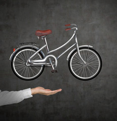 A hand in formal shirt holds a bicycle which is drawn on the black chalkboard wall. A concept of travelling.