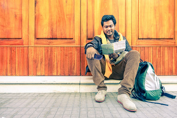 Young indian guy looking city map holding mobile phone - Asian model male next to old wooden door - Cheerful afro american student reading - Concept of tourism DIY and freedom - Soft vintage filter