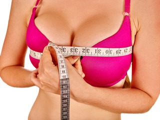 Girl in lingerie measures her breast measuring tape.