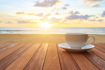 White coffee cup on wood table and view of sunset or sunrise bac