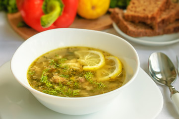 Homemade fish soup with tuna and rice served with dark bread and dill