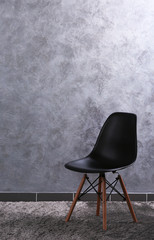 Modern black chair on grey wall background