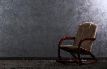 Comfortable rocking chair on grey wall background