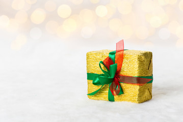 Golden Christmas gift box with shiny ribbon. Bokeh with glow effect on white background
