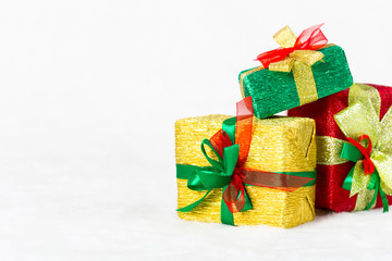 Red, green and golden Christmas gift box on white background