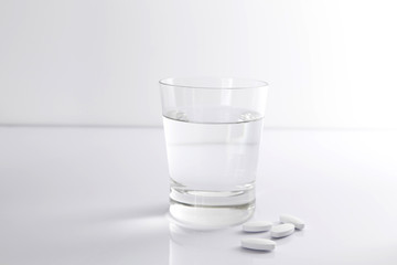 A glass of water and pills on a white background