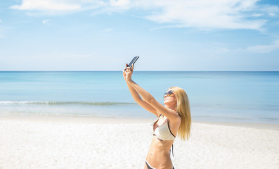 Young  female tourist taking selfie on the beach