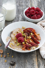 oatmeal with baked fruit and pistachios for breakfast, vertical