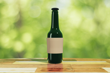 Black bottle with blank sticker on wooden table outdoor, mock up