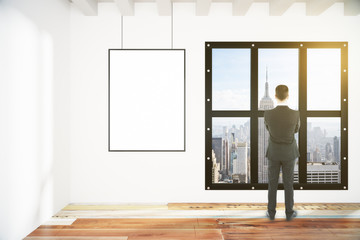 Blank white poster on white wall and businessman in empty loft r
