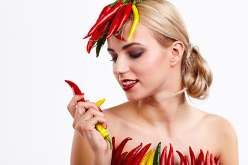 Spicy lady holding red and green hot chilli peppers in arms