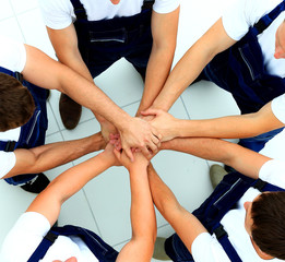 team of workers joining hands in circle