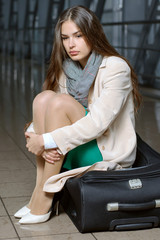 Girl waits flight sitting on suitcases