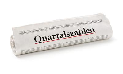 Zeitungsrolle mit der Überschrift Quartalszahlen