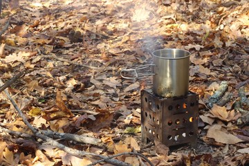 Tourist mini stove with a mug in the autumn forest