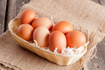 Eggs in Wicker basket on a wooden background