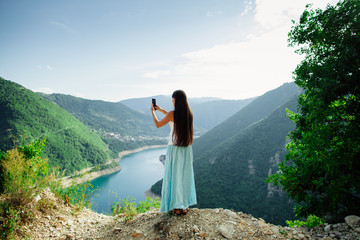 long hair girl taking photo of landscape