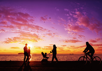 Silhouettes of people enjoying a walk by the seaside