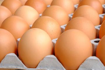 A dozen brown eggs in a carton on a wooden table