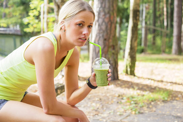 Woman after workout drinking smoothie
