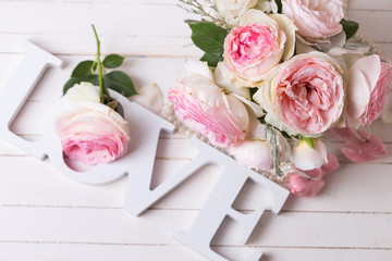 Sweet pink roses flowers  and word love on white painted wooden