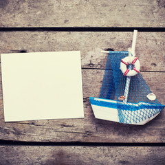 Decorative sailing boat and empty tag on  vintage wooden backgro