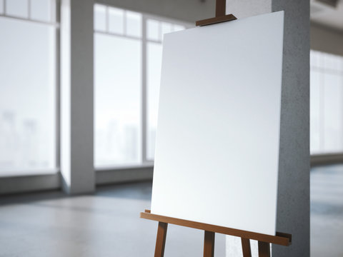 Wooden easel with a blank white canvas in modern interior.