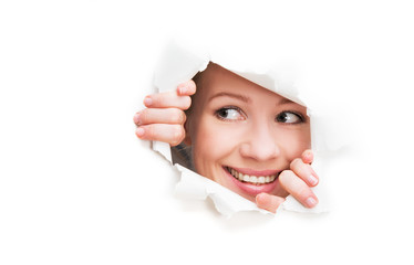 face of  woman peeking through a  hole torn in white paper poste