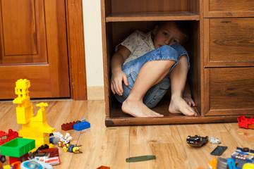 little boy hiding in a cupboard