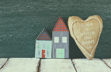image of vintage wooden colorful house and fabric heart on wooden table in front of  blackboard. faded retro filtered image