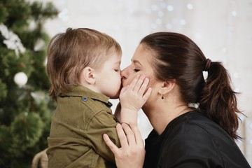 Holidays, christmas, love and happy family. Little boy kissing mother