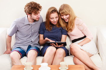 Friends relaxing browsing internet on tablet.