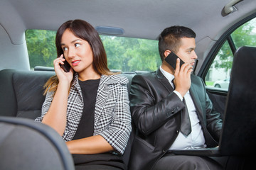 Young businesswoman and businessman sitting on the back seat of the car using mobile phones
