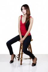 Attractive Slim Latina Woman Sitting On Stool