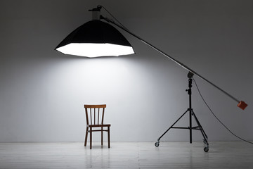 Preparation for studio shooting: empty chair and studio lighting