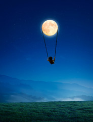 Little girl on a swing in the form of the moon