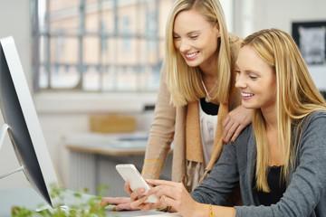 frau zeigt einer freundin eine nachricht am mobiltelefon