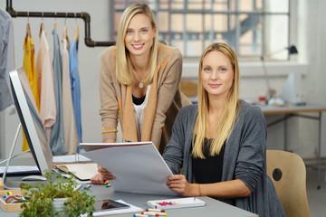 zwei motivierte junge frauen arbeiten in einem büro für modedesign