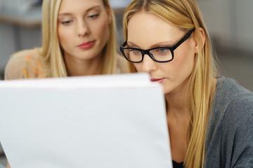 zwei junge frauen schauen konzentriert auf einen entwurf