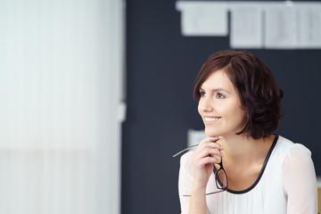 geschäfsfrau im büro lächelt in gedanken