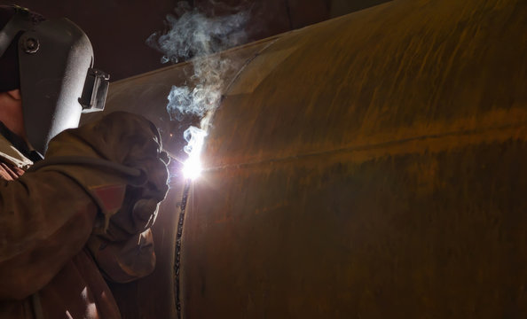welder performs welding large diameter pipe