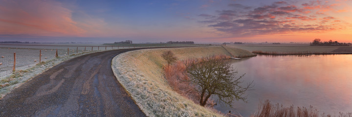Wall Mural - Typical Dutch landscape with a dike, in winter at sunrise