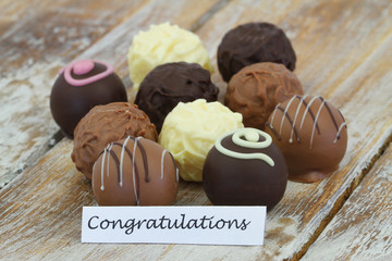 Congratulations card with assorted chocolates on rustic wooden surface