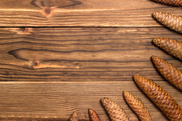 fir cones of different shapes and sizes on the wooden background
