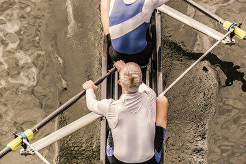 Top view of two athletic competition rower, who stroke their paddle through the water.