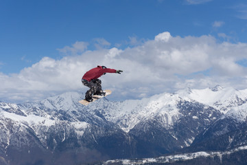 Flying snowboarder on mountains. Extreme sport