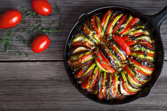 Vegetable ratatouille baked in cast iron frying pan homemade preparation recipe healthy diet french vegetarian food on vintage wooden table background. Top view