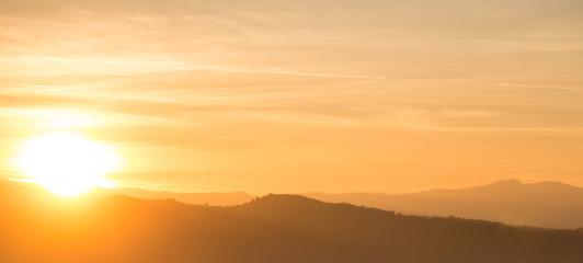 Orange sunset behind mountain range