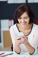 geschäftsfrau schaut lächelnd auf ihr mobiltelefon